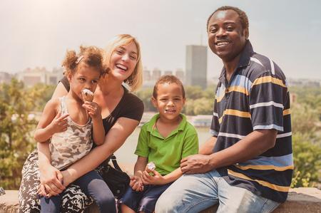 cornet: Outdoor portrait of happy international family enjoying and having fun while children eat ice cream cornet in front of city panorama Stock Photo