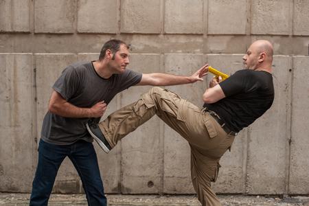 self defense: Kapap instructor demonstrates self defense techniques against a gun Stock Photo