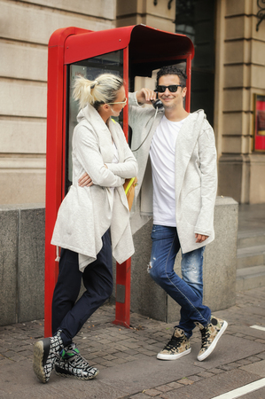 close together: Young couple enjoying a gossip as they stand close together in a phone booth Stock Photo