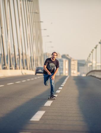 professional skateboarder riding a skate over a city road bridge