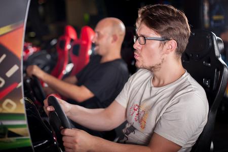 Jeune homme jouant roue motrice jeu vidéo dans la salle de jeu