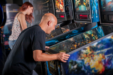 Young man playing pinball in game room Stockfoto