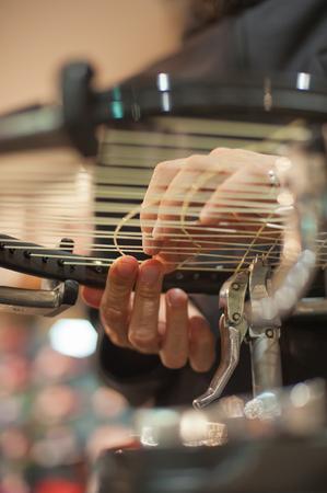 Stringing Machine. Close up of tennis stringer hands doing racket stringing in his workshop