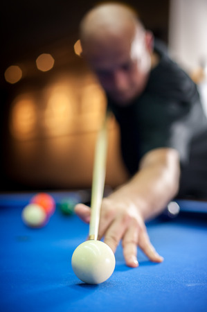 Young man playing billiard in a pool hall Stock Photo