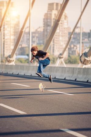 Skater doing tricks and jumping on the street highway bridge, through urban traffic. Free riding skateboard