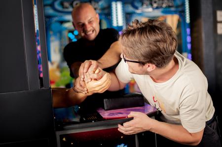 jugando videojuegos: Dos de los amigos que se divierten en la sala de juegos Foto de archivo