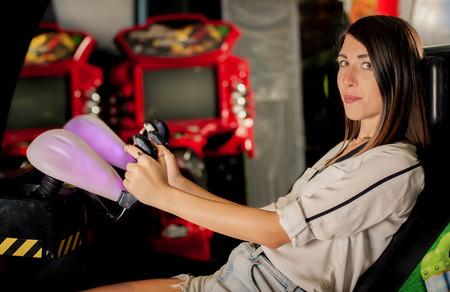 jugando videojuegos: Mujer que juega a juegos pequeños en la sala de juegos