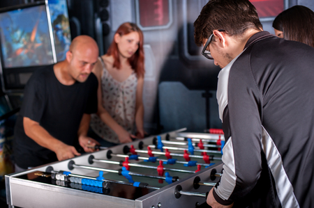 Group of friends playing soccer table foosball Stockfoto