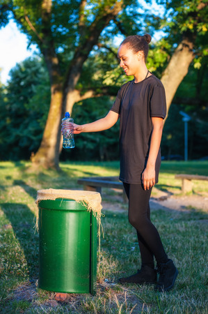 conscience: Girl throws trash in the public litter bin in the city park. Preserve nature