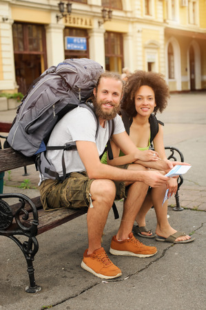 A couple of backpacker tourists sitting on a bench and waiting to board a train at the railway station