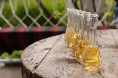 Plum brandy in shot glasses on wooden table. Outdoor shot Stock Photo