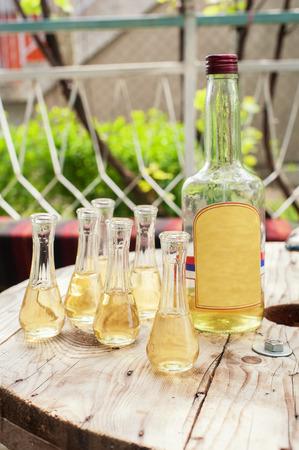 rakia: Bottle of plum brandy with small glasses on wooden table. Outdoor shot Stock Photo