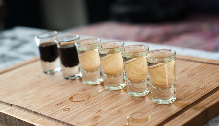 Brandy in shot glasses lined up in a row on wooden tray Stock Photo