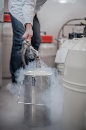 Liquid nitrogen technician fills cryogenic container