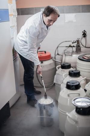 nitrogen: Liquid nitrogen technician fills cryogenic container