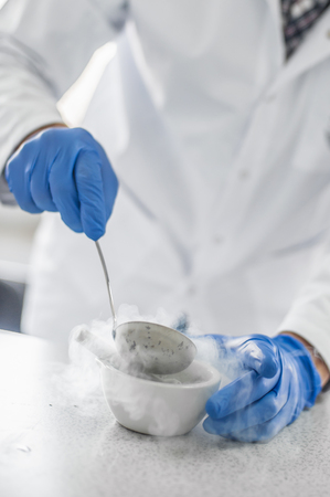 Laboratory technician performs an experiment with liquid nitrogen in laboratory mortar with pestle and ladle spoon
