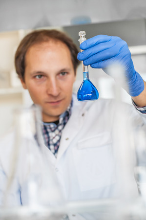 Male medical or scientific laboratory researcher performs tests with blue liquid. Close up