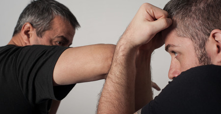 krav maga: Kapap instructor demonstrates fighting techniques with his student Stock Photo