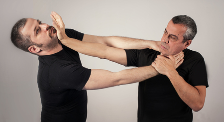 Kapap instructor demonstrates street fighting self defense technique against holds and grabs with his student Stock Photo - 68876853