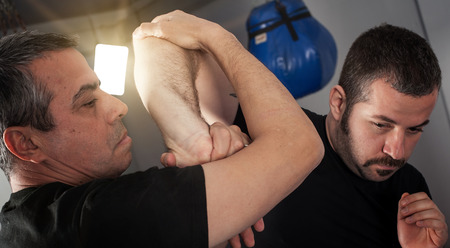 krav maga: Kapap instructor demonstrates street fighting self defense technique against holds and grabs with his student