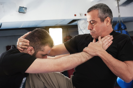 aggressor: Kapap instructor demonstrates street fighting self defense technique against holds and grabs with his student