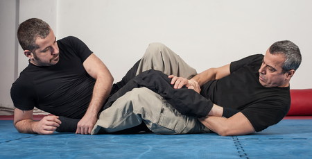 grappling: apap instructor demonstrates ground fighting techniques with his student Stock Photo