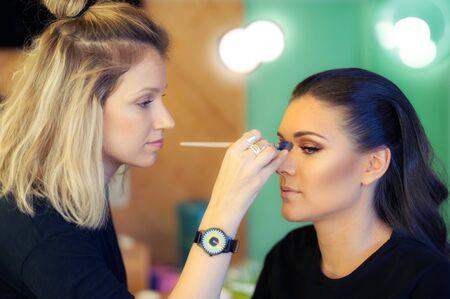 tonal: Makeup artist applying liquid tonal foundation on the face of the woman