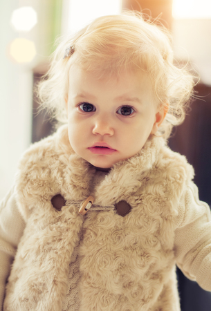 Cute baby girl posing indoors in fancy clothes Stock Photo