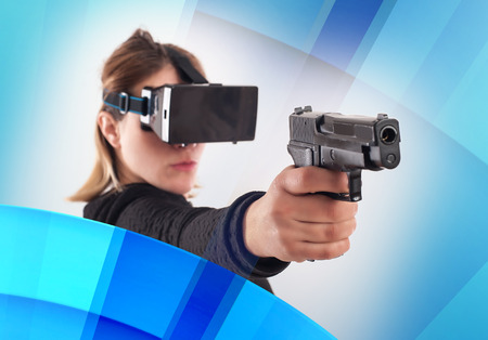 Woman play VR shooter game with virtual reality gun and vr glasses. Studio shoot. Stock Photo