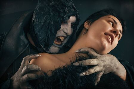 Scary vampire devil biting young woman. Medieval gothic nightmare horror. Studio shoot