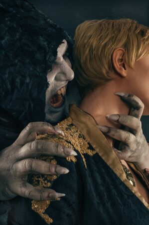 fandom: Ancient monster vampire demon holds beautiful woman and preparing to bites her neck. Halloween fantasy concept Stock Photo