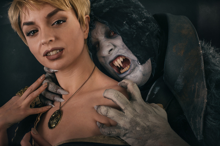 Ancient monster vampire demon holds beautiful woman and preparing to bites her neck. Halloween fantasy concept Stock Photo