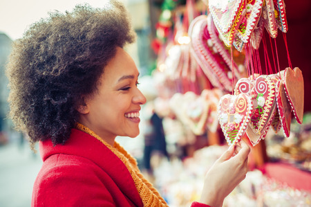 Portret of beautiful woman buying gingerbread hearts in gift shop