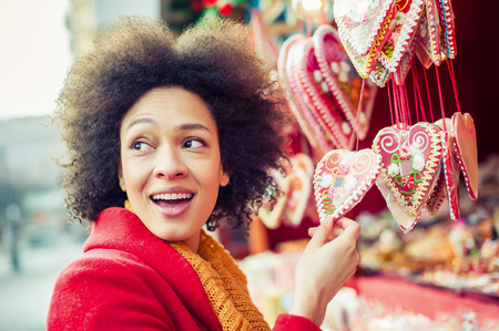 portret: Portret of beautiful woman buying gingerbread hearts in gift shop