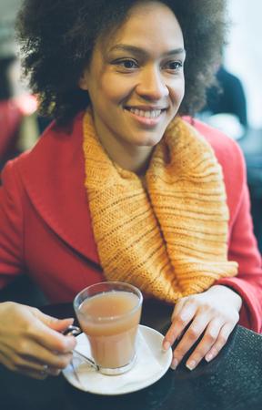 Portrait of beautiful young woman enjoying tea in a restaurant