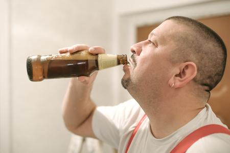 Portrait of construction mason worker drinking beer during working break