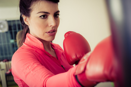 Woman with red boxing gloves training on a punching bag in the gym