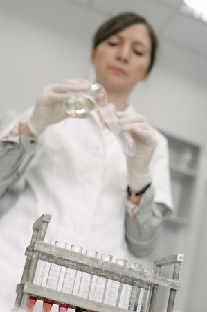 Medical laboratory scientists holding a test tube with sample in the medical or scientific laboratory