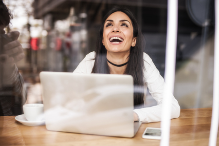 Woman in love drinks coffee and chat on laptop computer. Emotional expression