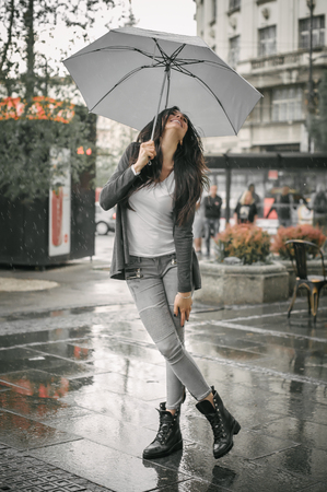 雨の中で傘の下で幸せな笑顔の女性の肖像画
