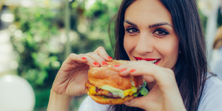 Portrait of a young happy woman eating tasty fast food burger Stock Photo