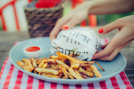 Woman serving burger with french fries on a plate. Close up