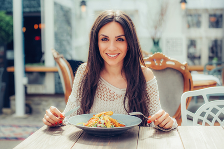 Young woman enjoying food in a restaurant, having her lunch break. Close up