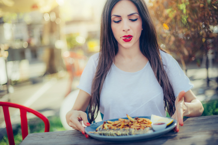 Young woman eating fresh tasty fish with french fries on wooden table