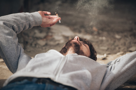 Closeup of young man lying on the ground and smoke marihuana grass or hashish joint cigarette