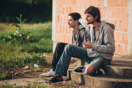 Two friends sitting on stairs and smoking cannabis or hashish joint in abandoned ghetto part of the city Stock Photo