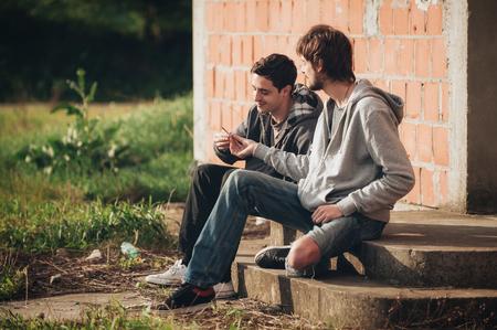 도시의 버려진 빈민가 부분에있는 계단에 앉아서 흡연 대마초 또는 해시시 공동 두 친구