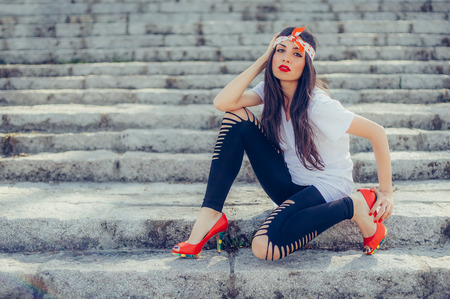 Beautiful and pretty fashion style long hair woman posing on the stairs