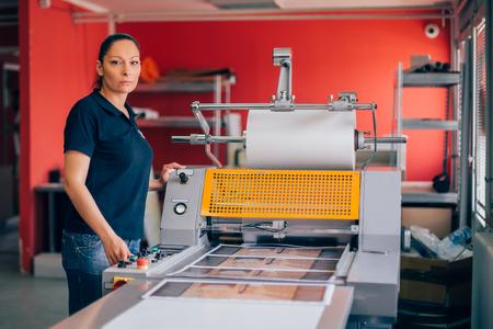 印刷工場で働く若い女性。印刷機 写真素材