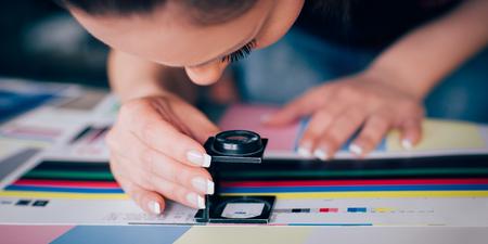 Pracownik w centrum drukarskim i prasowym używa lupy i sprawdza jakość wydruku